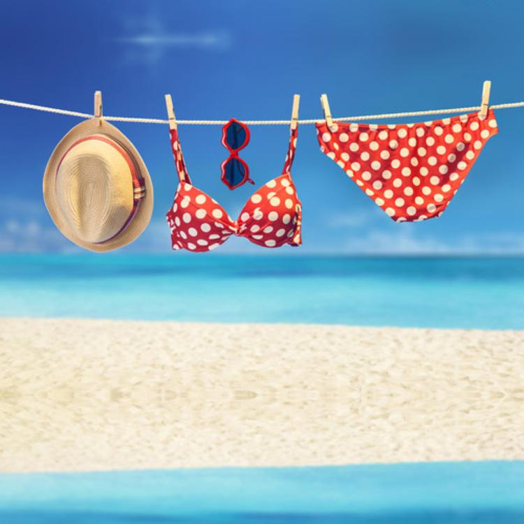 badkleding aan waslijn, op strand met hoed en zonnebril